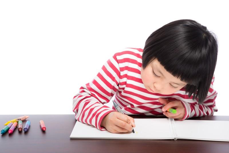 カラーペンで厚紙に絵を描く子供