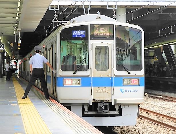 小田急線駅ホームに停車する後尾車両と車掌