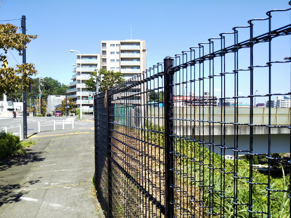 小田急線の車両基地が見える大妻女子大学多摩キャンパス前の歩道