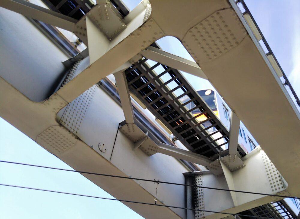 京王線のホームから見える、真上を走る多摩モノレールのタイヤ