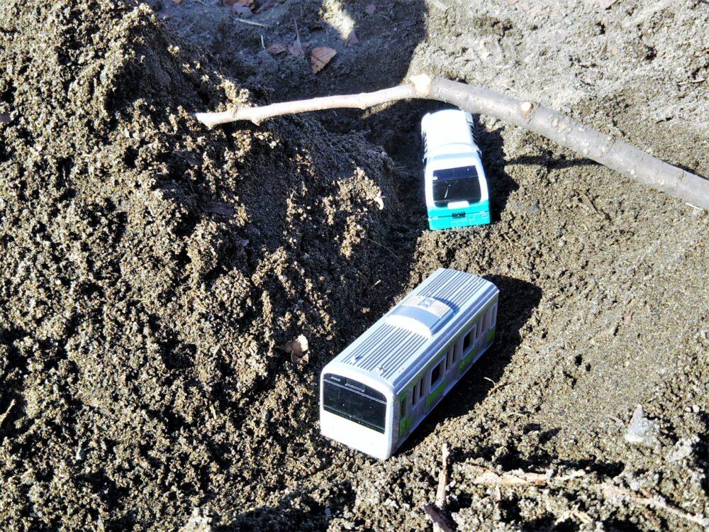 砂の山の間を走る電車のおもちゃ