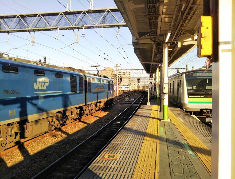 JR八王子駅の横浜線の橋本・桜木町方面・先頭車両側ホームと電車、隣の線路には貨物列車ブルサンダーが停車