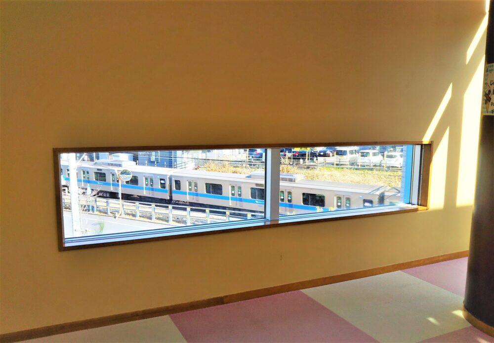 子どもセンターまあちの低い場所にある窓と、窓から見える小田急