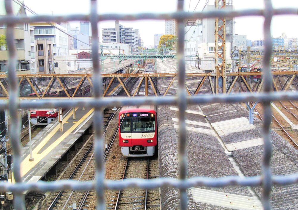 跨線橋から見える神奈川新町駅ホームに停車中の電車