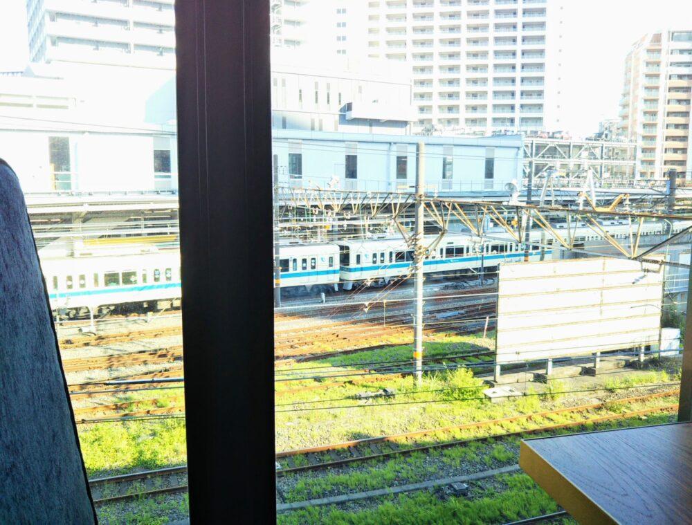 ロマンスカーミュージアムのカフェ店内(ソファ席から見える海老名駅と通勤電車)