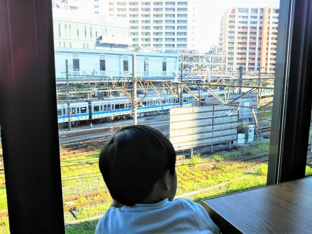 ロマンスカーミュージアムのカフェ店内(ソファ席から見える海老名駅と電車