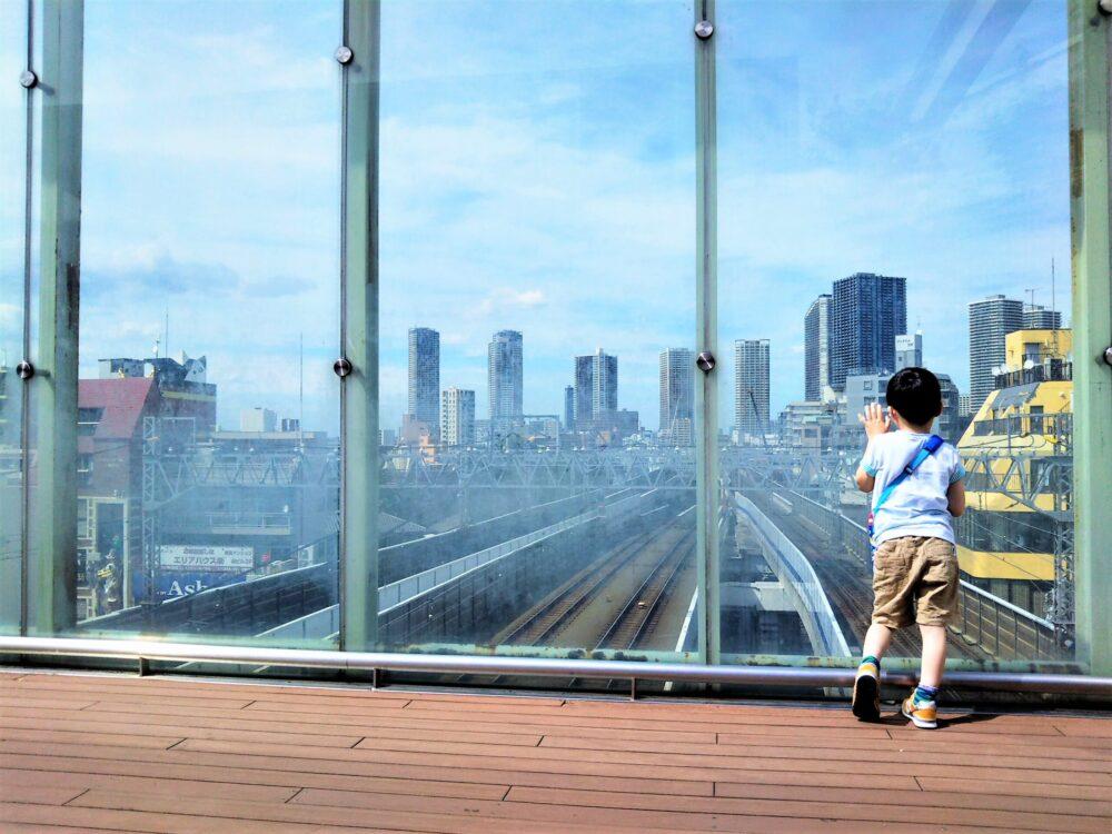 東急線の元住吉駅にある屋上庭園で電車を眺める子供