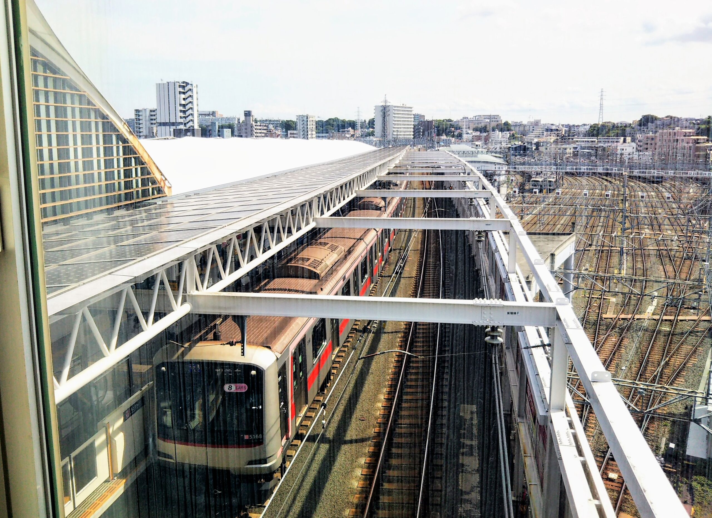 東急線の元住吉駅の改札フロアで見える車両基地とホームに停車する電車